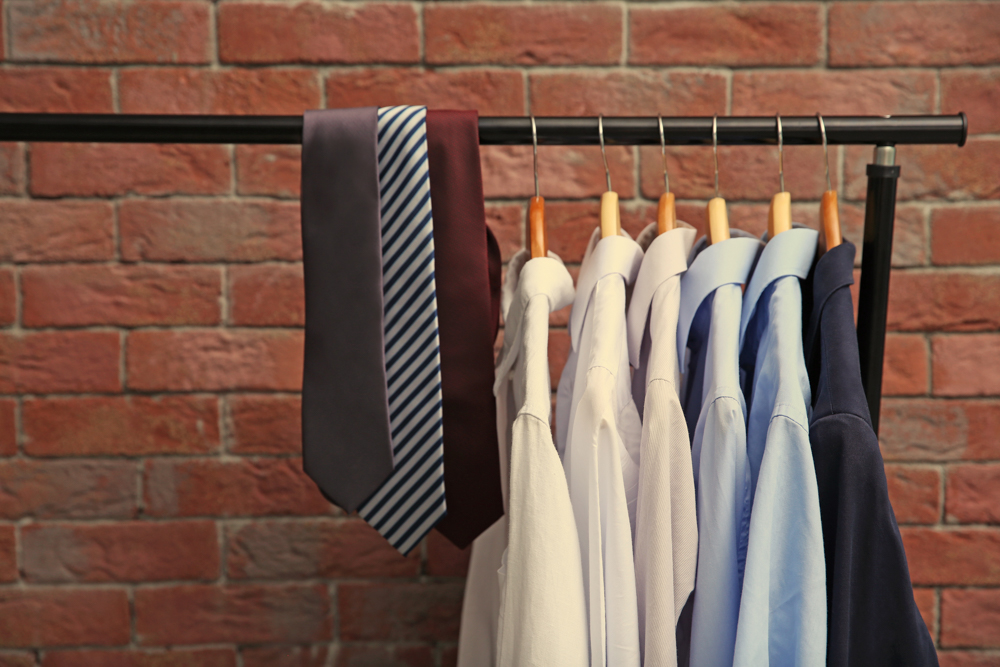 Hangers,with,male,shirts,and,ties,on,clothes,rail,against