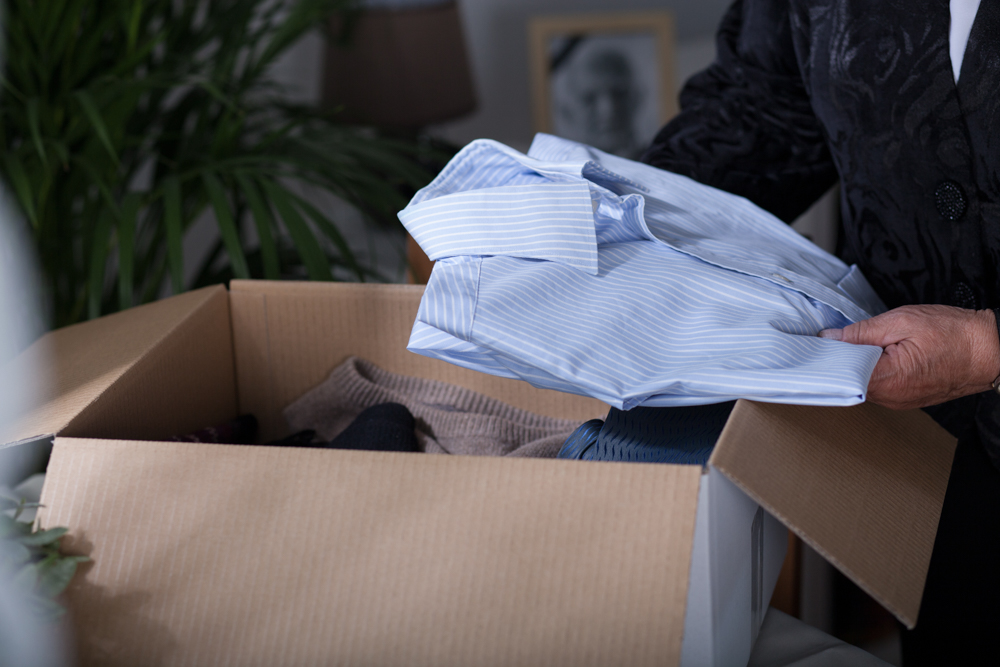 Woman,putting,her,dead,husband,clothes,into,a,box