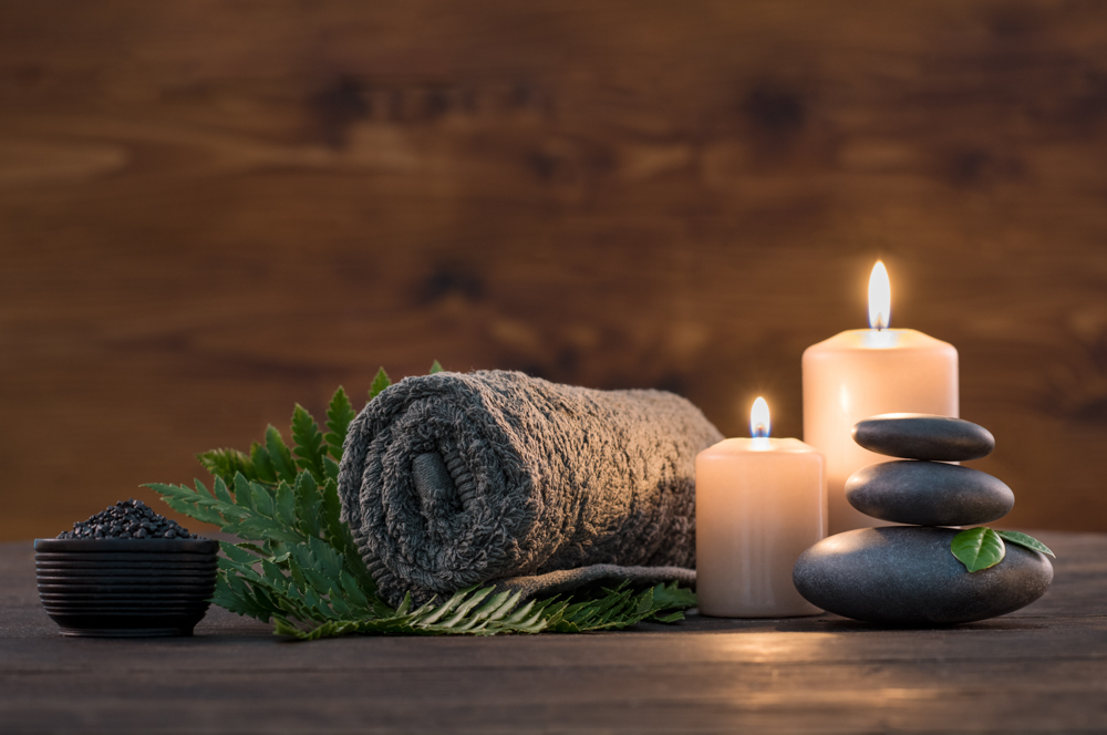 Towel,on,fern,with,candles,and,black,hot,stone,on