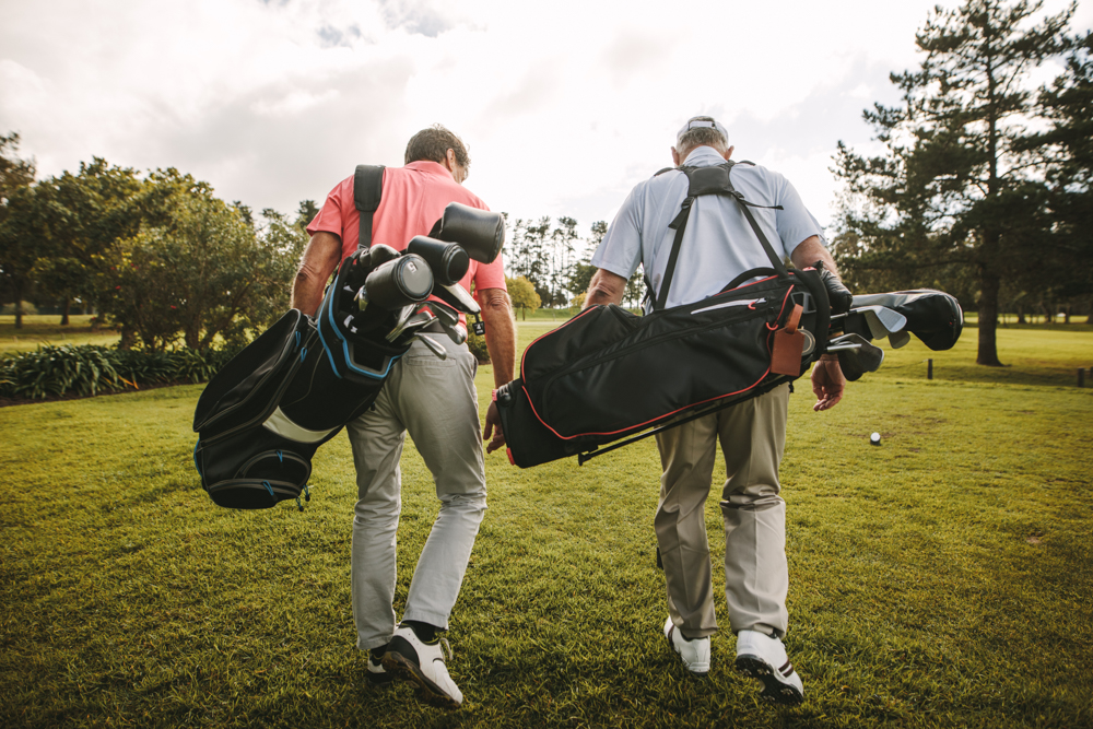Rear,view,of,two,senior,golf,players,walking,together,in