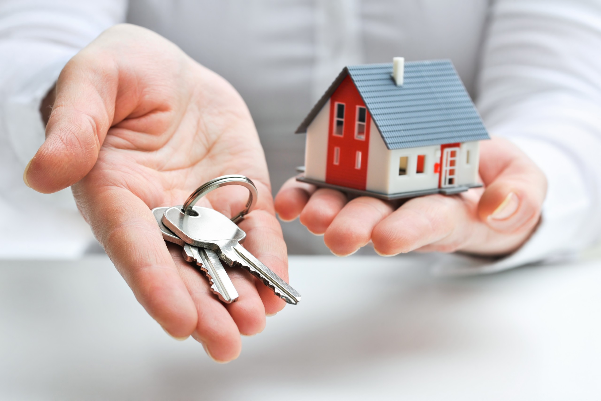 Real,estate,agent,with,house,model,and,keys