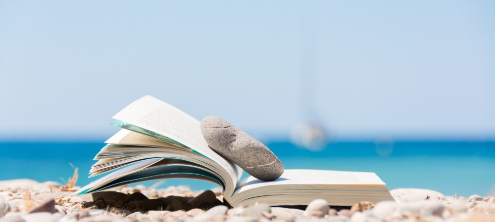 Reading,in,summer,vacation,,concept.,book,on,the,pebble,beach